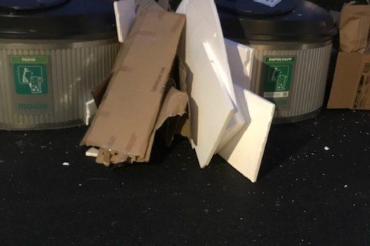 Søppel utenfor avfallsbrønnene